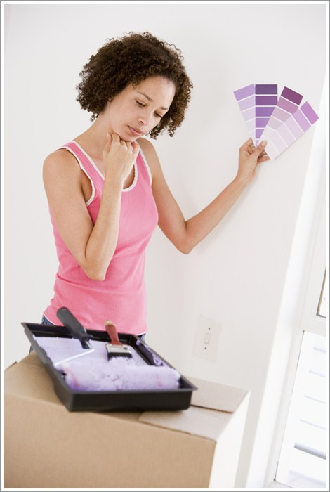 Woman with paint swatches in new home thinking