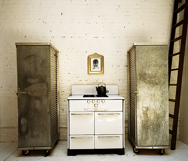 Next to the worktop of the large kitchen, a classic stove lies between two pantries from camp