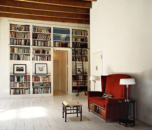 It was designed by the owner; the red sofa features a high back and shelves for books.