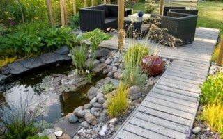 A beautiful small pond and a patio with a sitting area